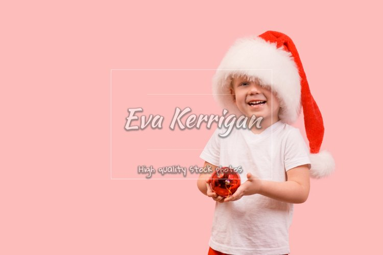 Boy child Toddler in hat of Santa Claus holds New Year ball. example image 1