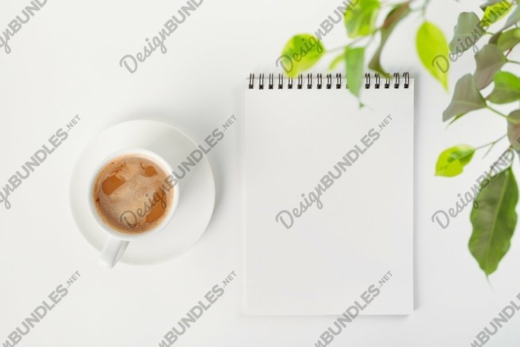 Open notebook with a blank sheet and mug of coffee example