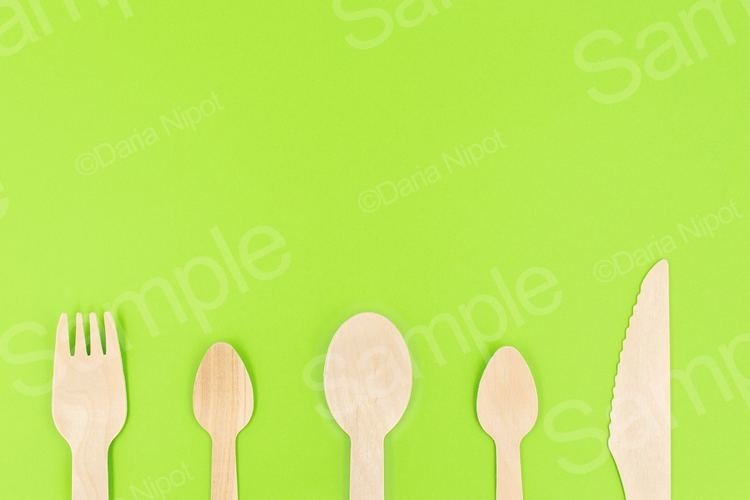Eco friendly disposable cutlery on green background example image 1