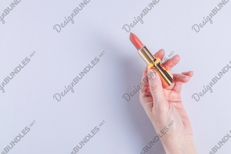 A female hand holds an open case with bright pink lipstick