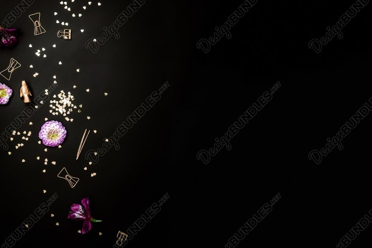 Flat lay scene with gold colored items on black background example image 1