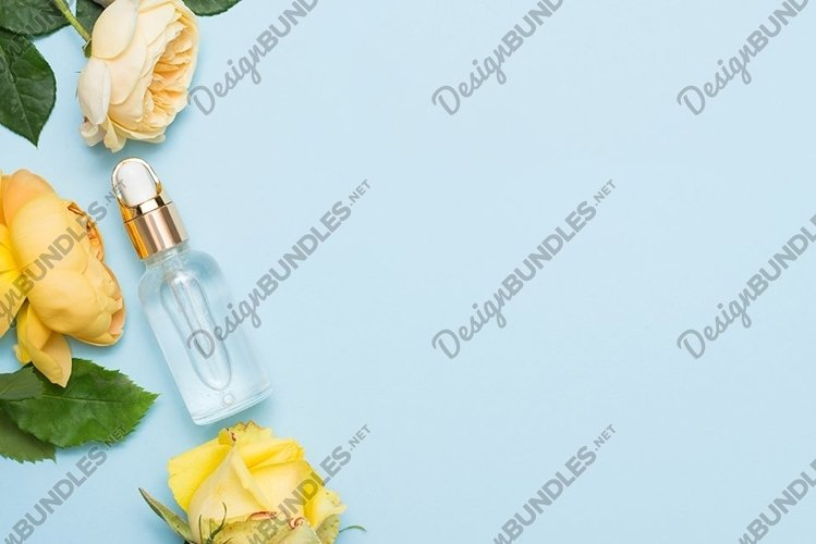 Natural cosmetic oil with yellow roses on blue background example image 1