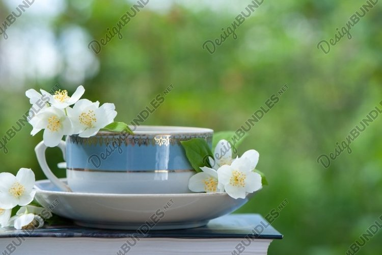 Summer composition of a cup of tea, book and Jasmine
