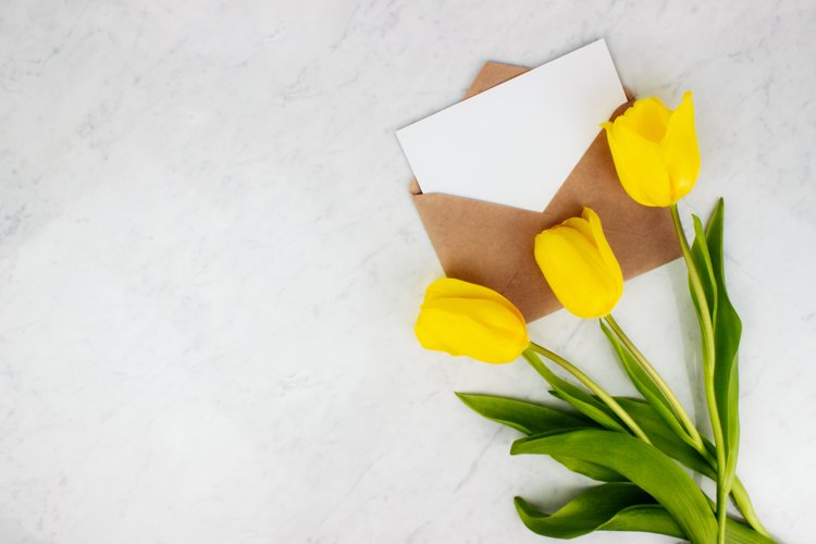 Yellow tulips with envelope and letter on marble background