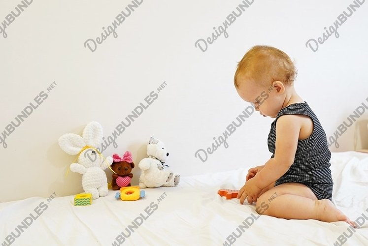 Cute little baby with group of plush toys playing on a white example image 1