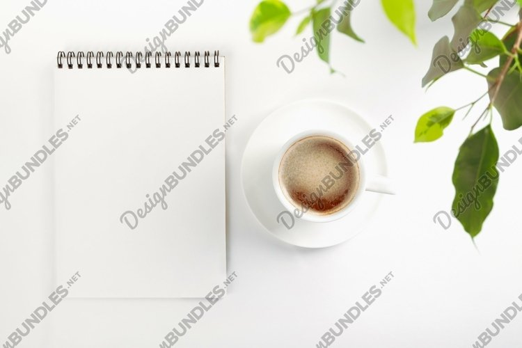 Open notebook with a blank sheet and mug of coffee example 1