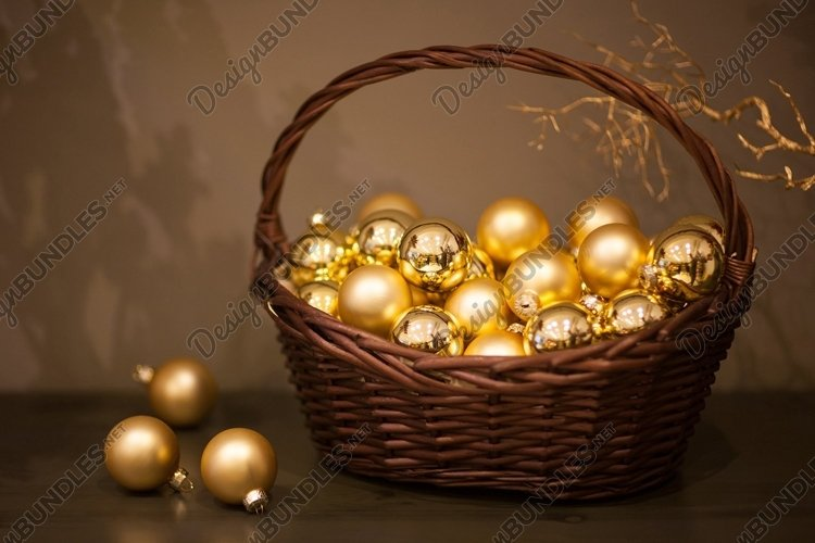 Shiny Christmas tree toys golden color in a wicker basket example image 1