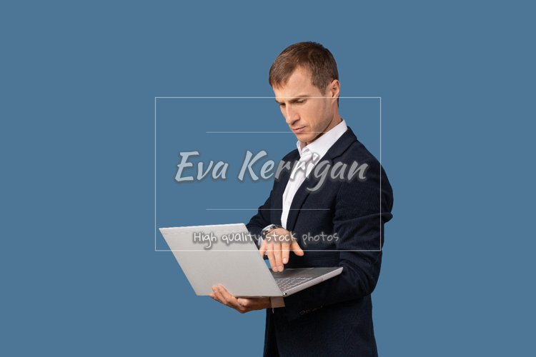 Man businessman in business suit looks at laptop. example image 1