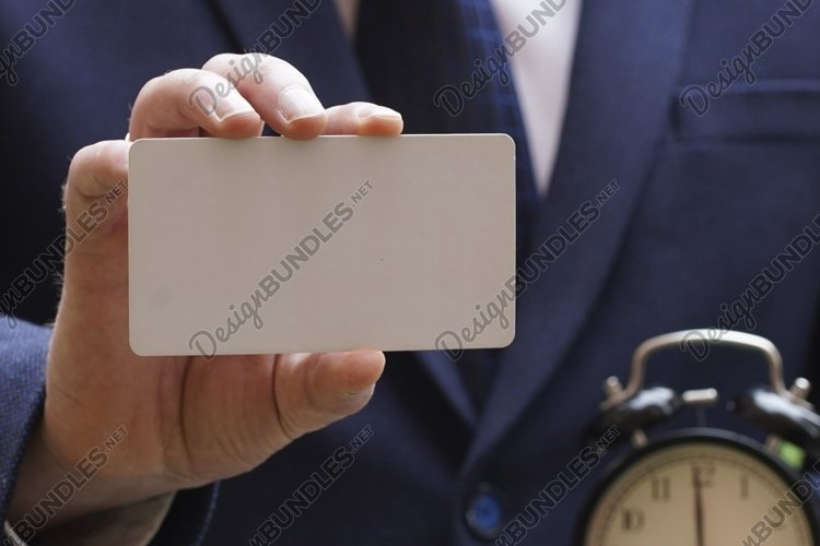 Blurred businessman's hand showing business card example image 1