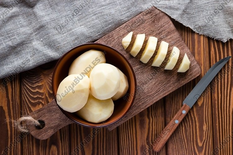 peeled sliced potatoes on a cutting board example image 1