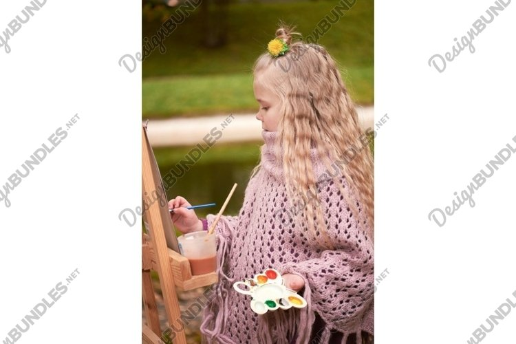 ittle girl painting a picture in the park example image 1