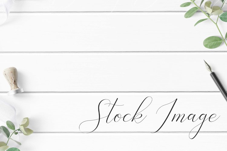 Styled Stock with greenery and white ribbon on white wood. example image 1