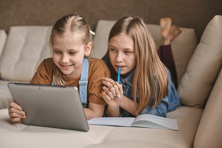 Two girls play with a tablet at home, distance learning example image 1