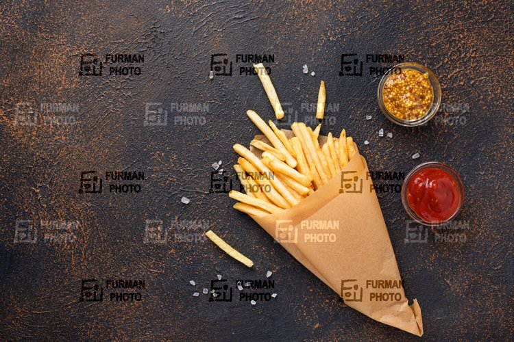 French fries in a paper bag with sauces example image 1