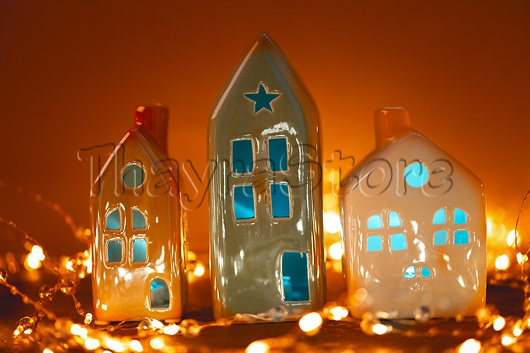 Christmas candle houses against bokeh lights background. example image 1