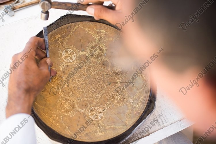 Craftsman engraving patterns on the tray. Masters of Asia