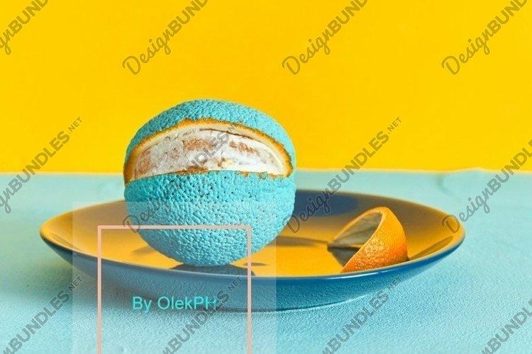 Painted orange in blue on a plate. peeled slice of peel example image 1