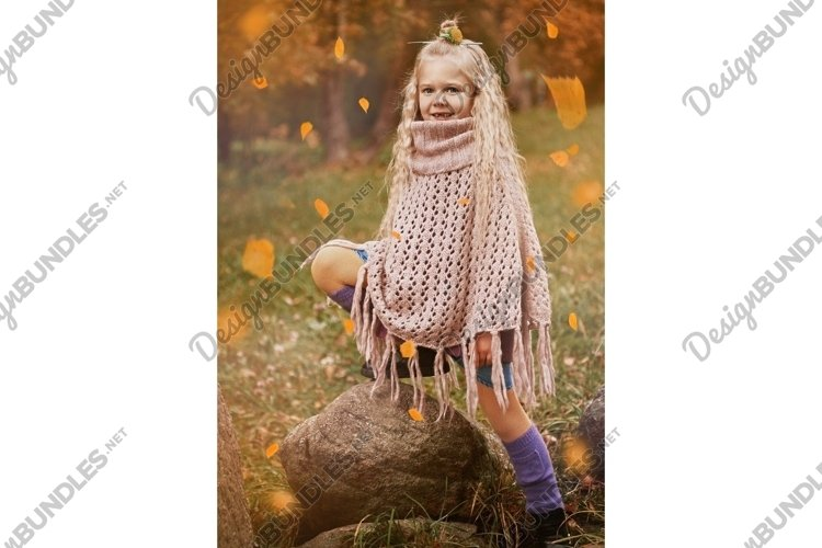 autumn portrait of a cute little girl wrapped in a big scarf example image 1