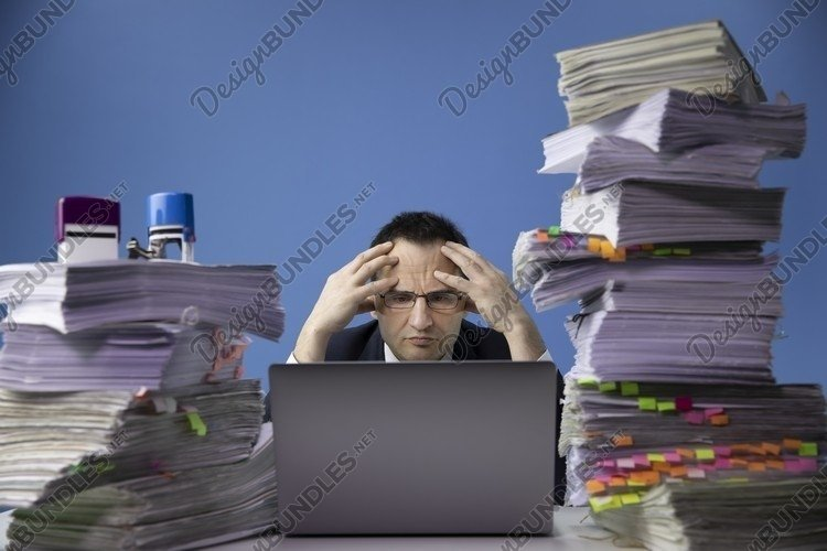 businessman sitting at office desk with stack of documents example image 1