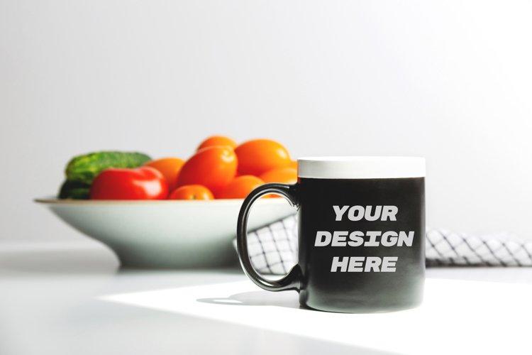 Black coffee mug mockup on kitchen table. Cup mock up